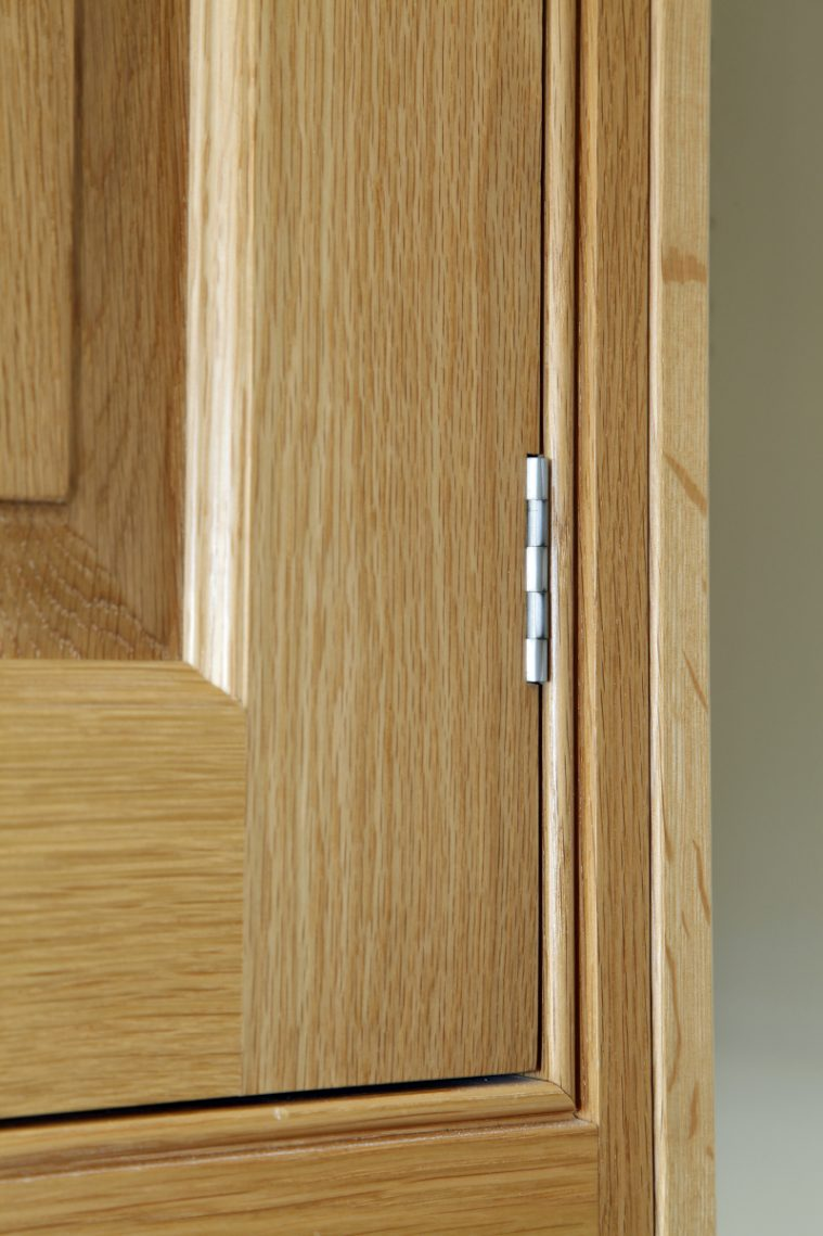 A Close-up Of An In-frame Kitchen Cabinet Showing The Exposed Butt Hinge